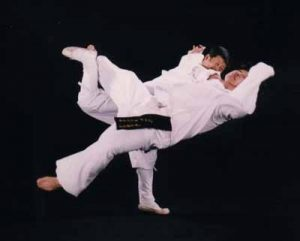 Simultaneously strike neck and hook leg to throw at Sydney Hapkido dojang.